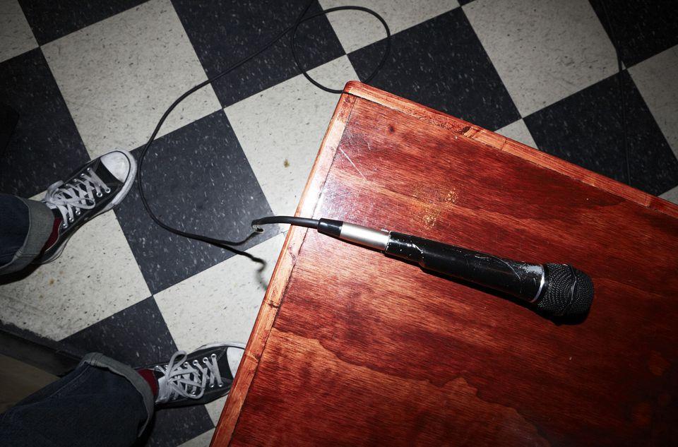 Feet of mature man next to microphone in karaoke bar