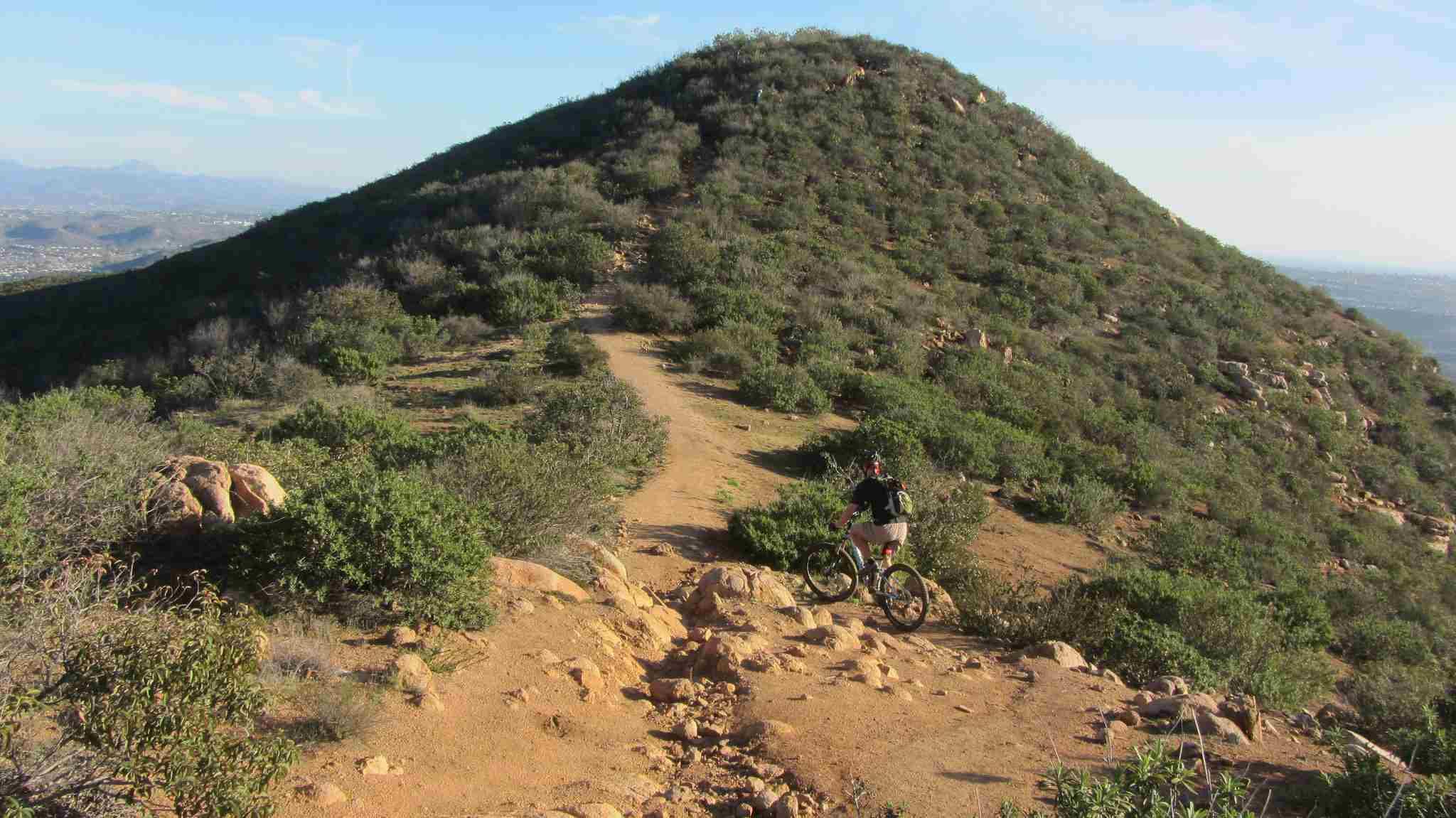 Mountain biker climbs up towards North Fortuna peak, Mission Trails Regional Park