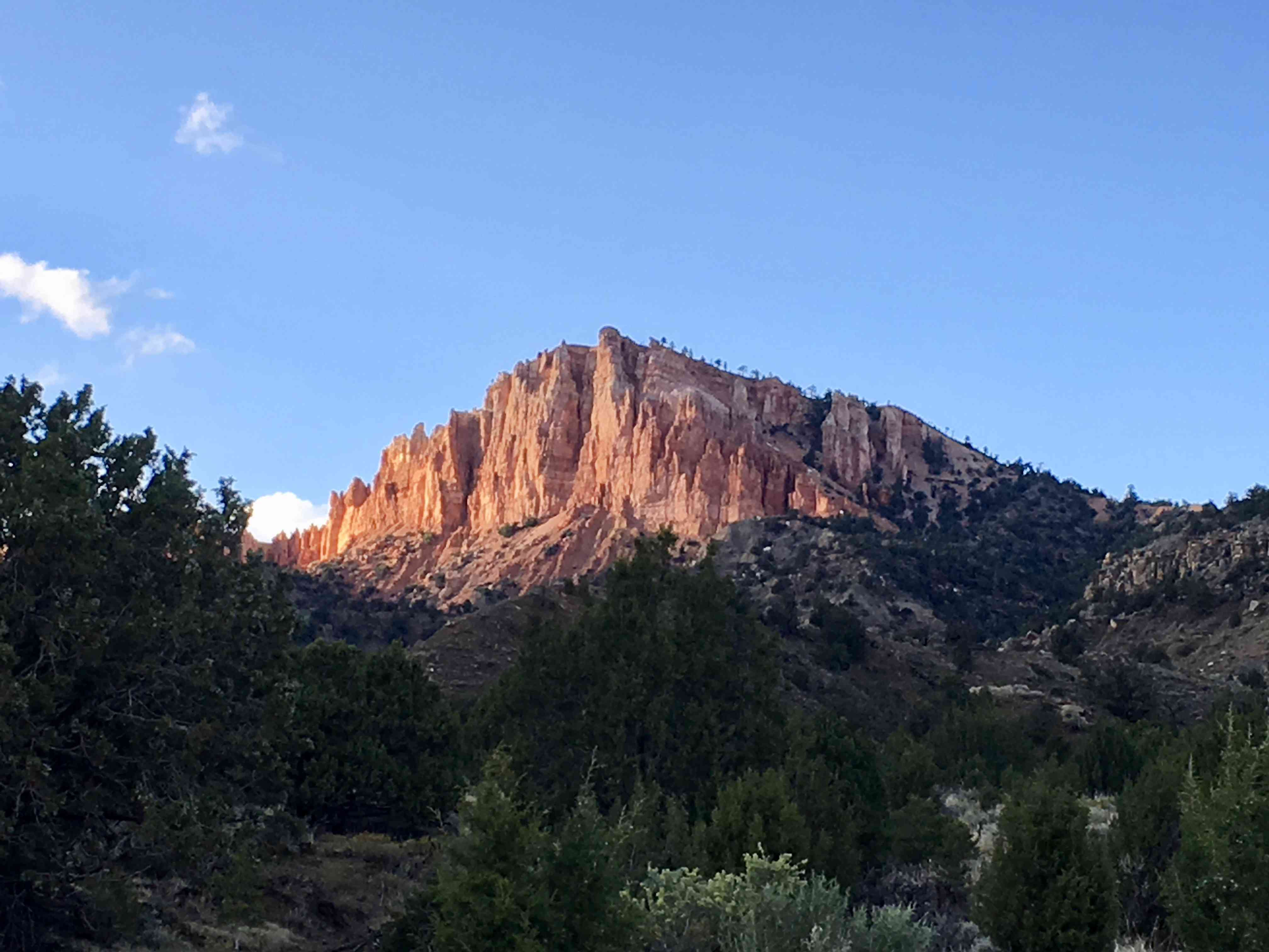 A red cliff face is illuminated by the morning sun in Bryce Canyon