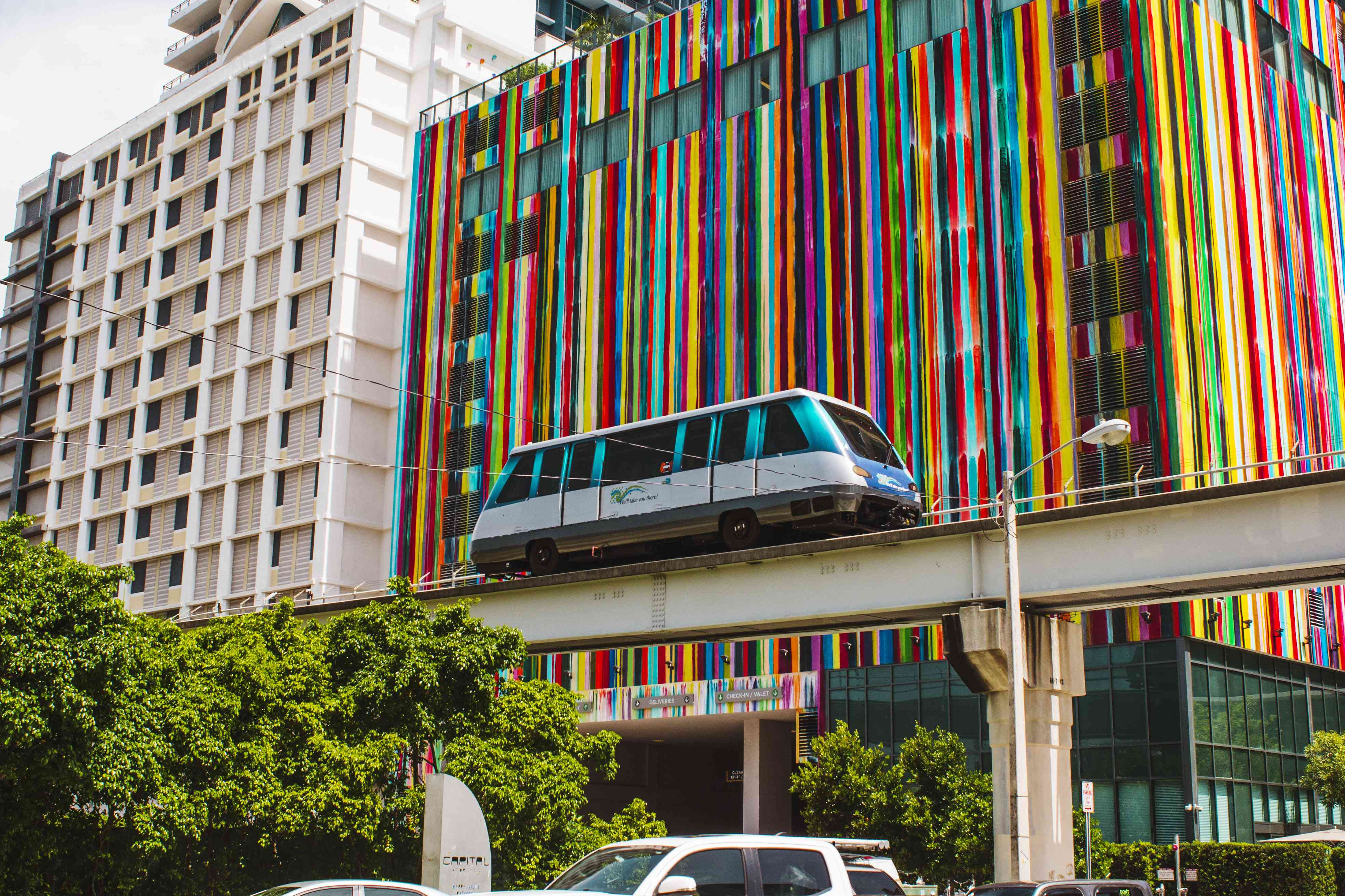 MetroMover driving by colorful buildings in Brickell