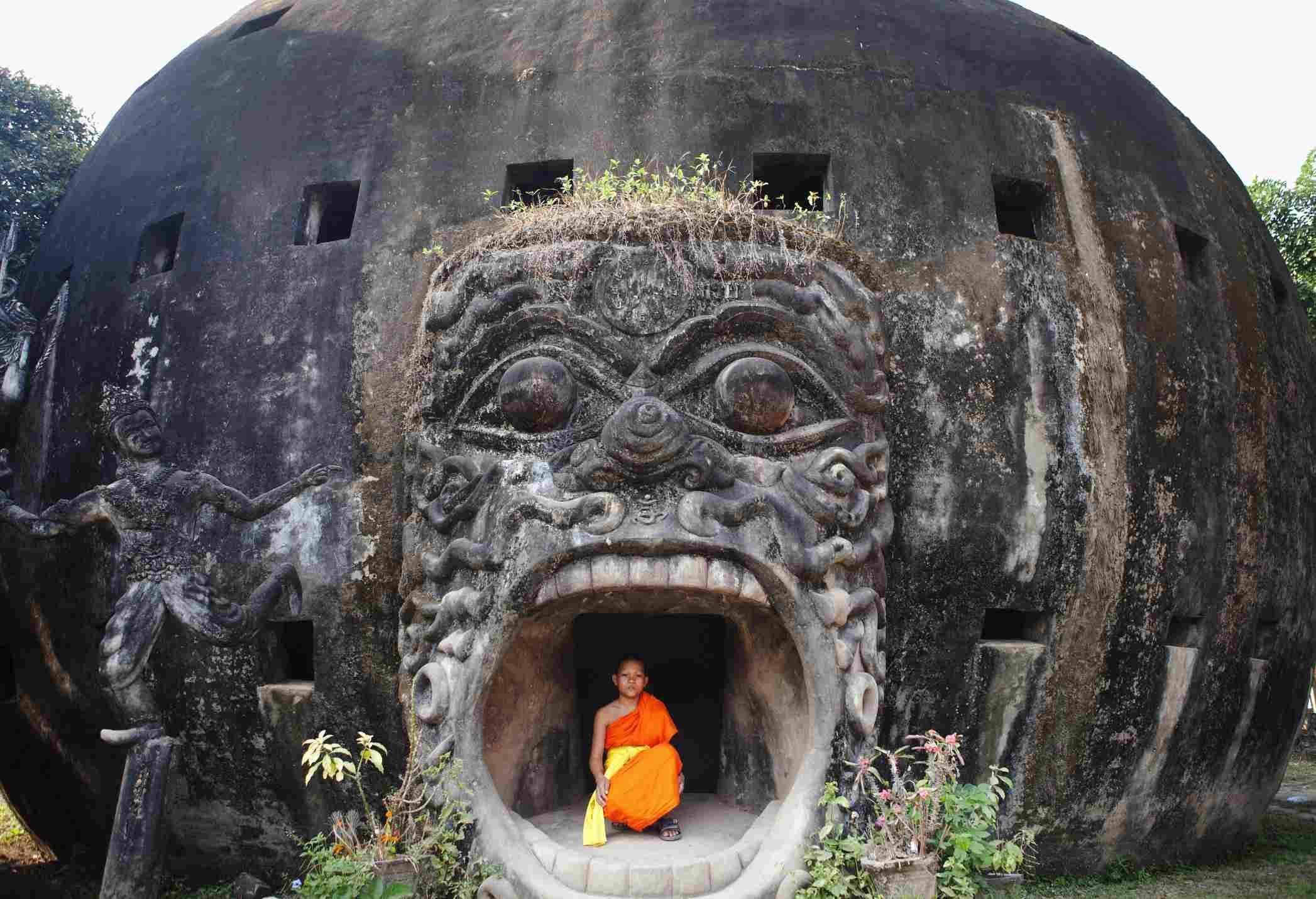 Monk posing in Buddha Park statue