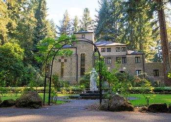 stone building in a park surrounded by trees with a white statue out from