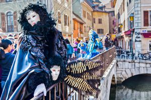 Person In Costume And Mask Leaning On Railing By Canal During Carnival In City
