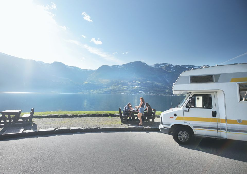 Family eating lunch out of campervan near lake and mountains