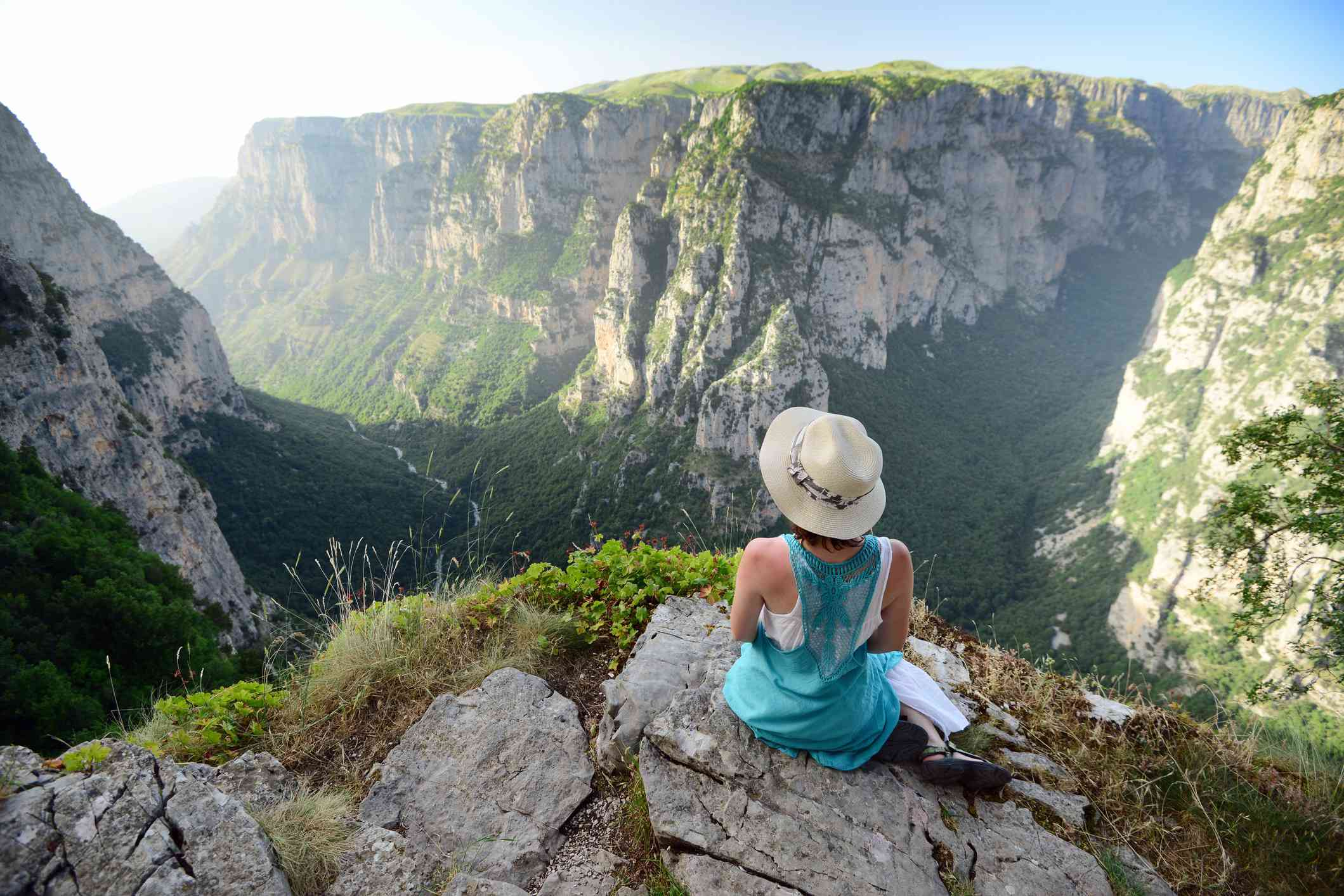 Young woman with blue dress and hat sitting over Vikos gorge, Timfy mountain, Zagoria / Epirus, Greece