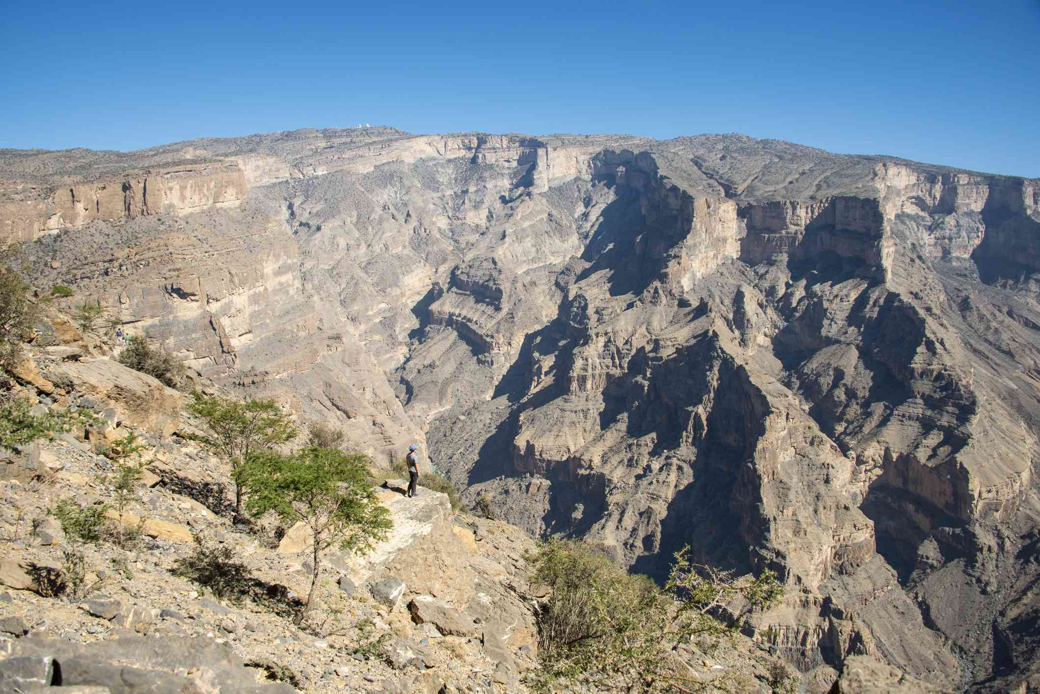 Distant view of a man at the top of Jebel Shams with a canyon in the distance