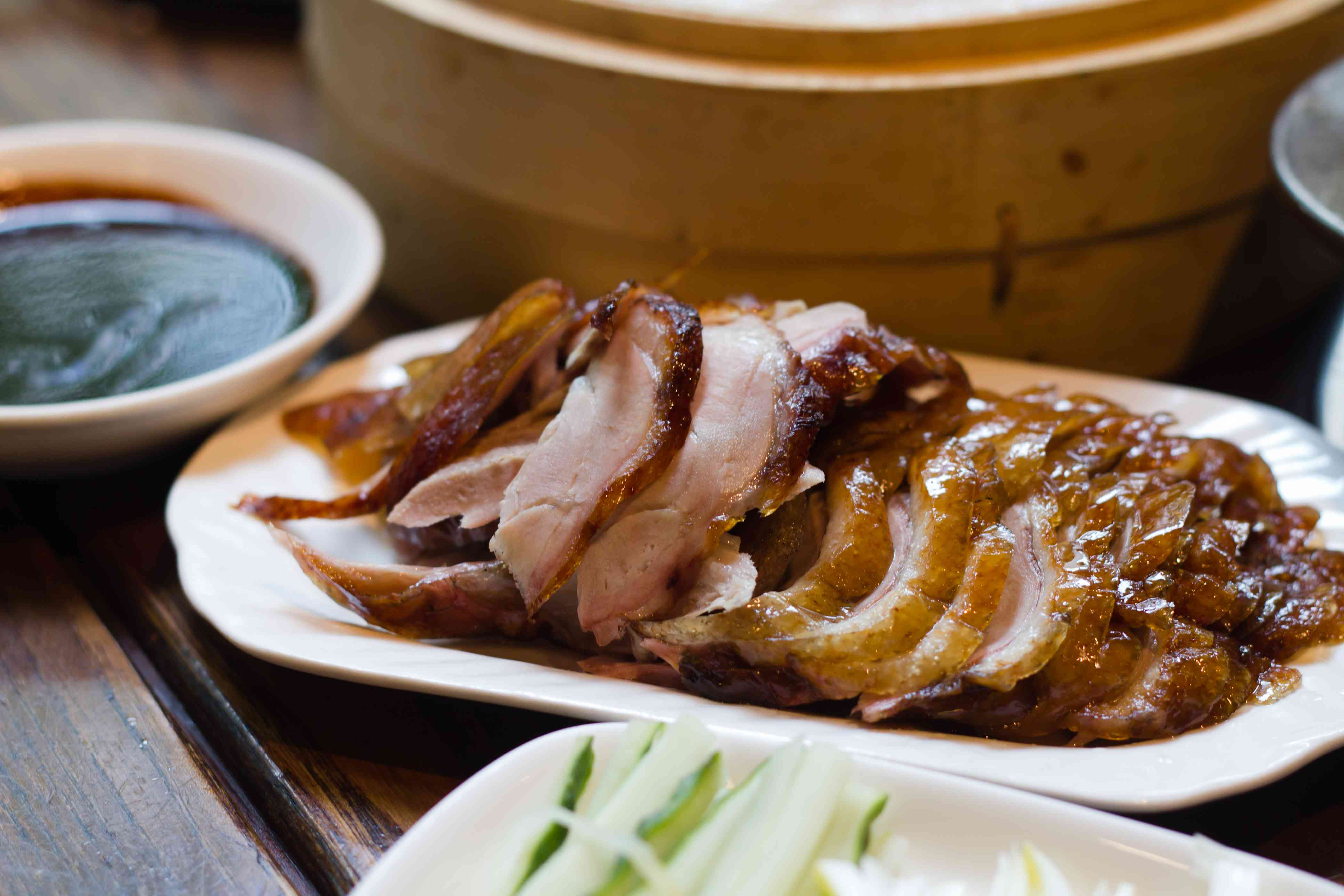 Cena de pato en rodajas asadas de Beijing en un plato blanco con lados