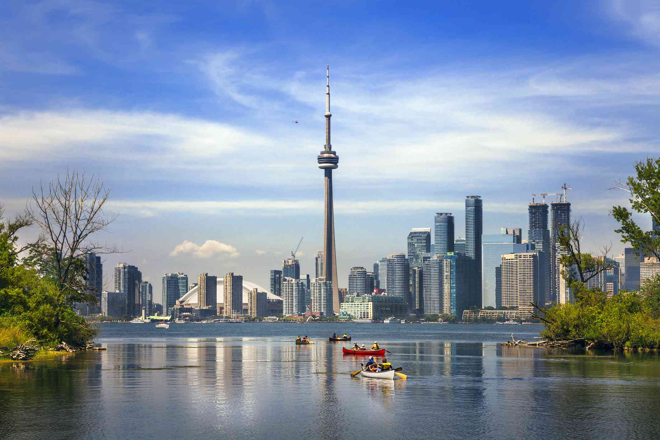Kayakers in a large body of water with the Toronto skyline in the background