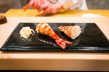 Boiled prawn sushi with pickled ginger on a flat, black plate