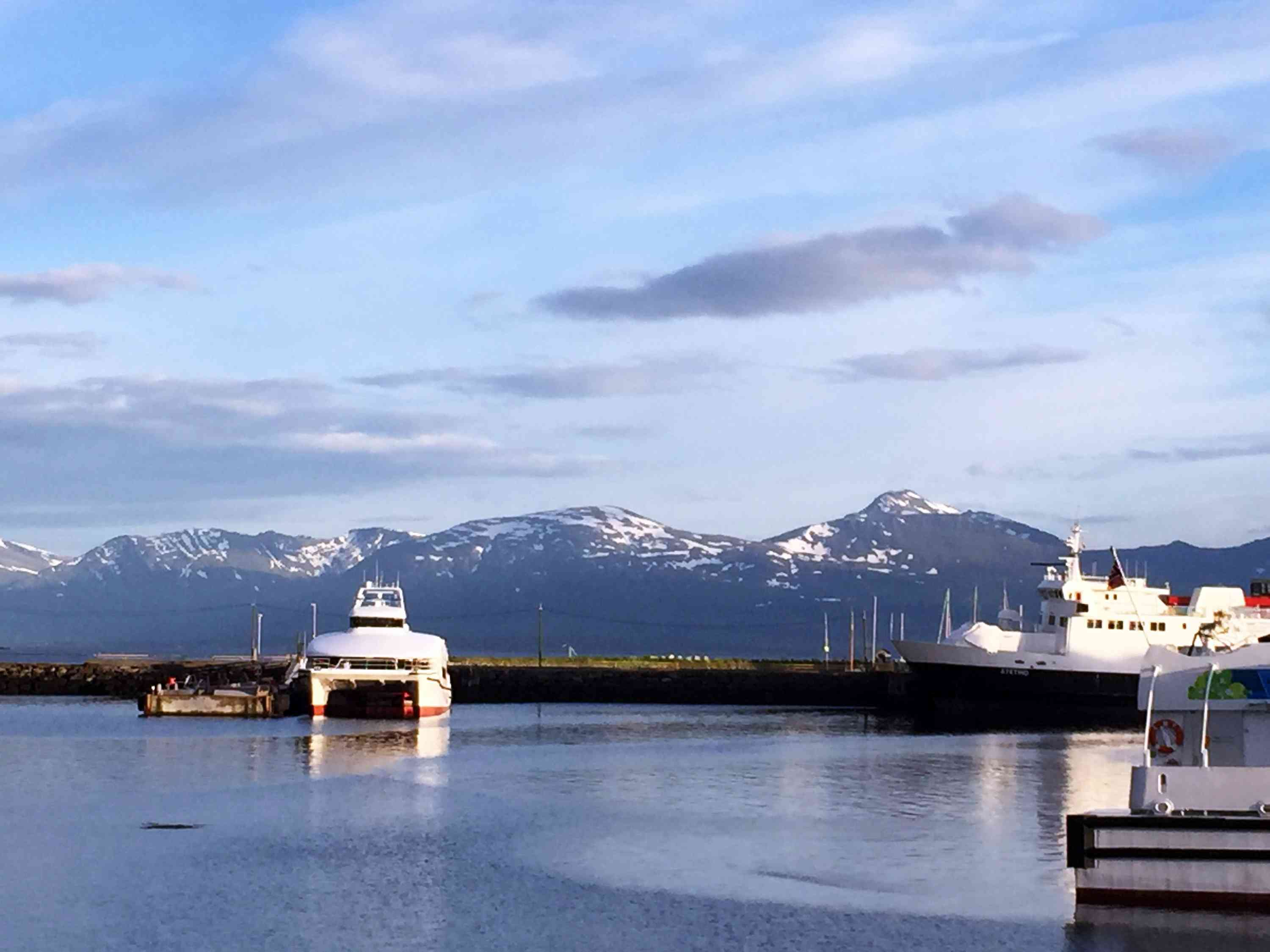 Harbor with boats and ice capped mountains in distance