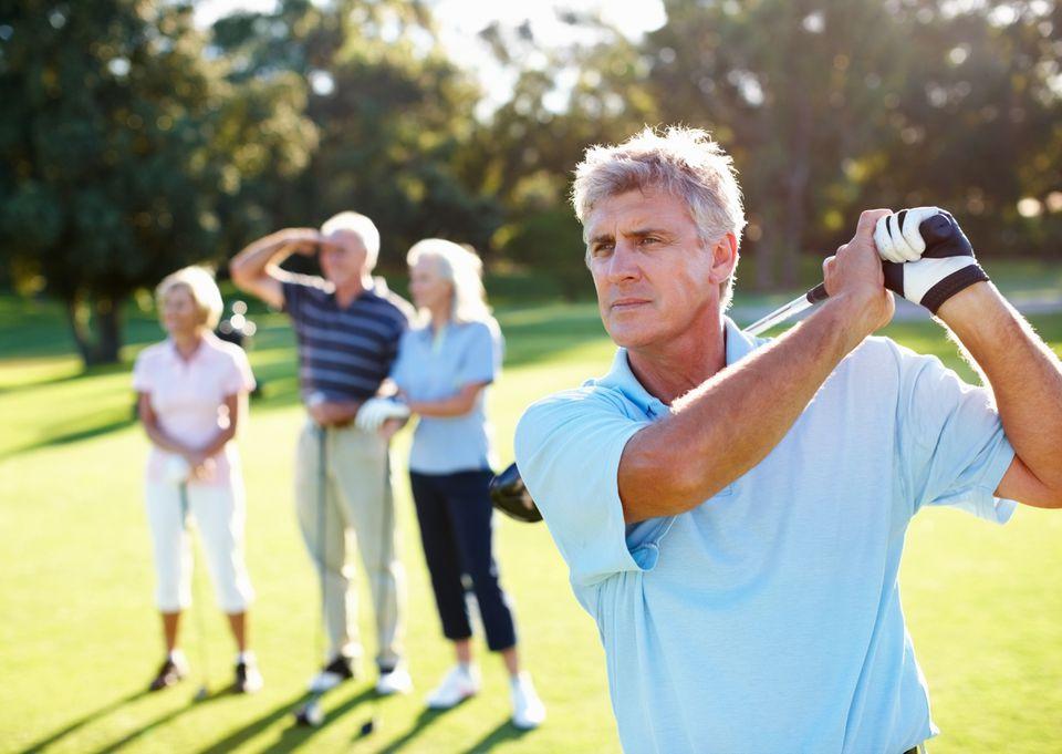 Smart, mature golfer swinging