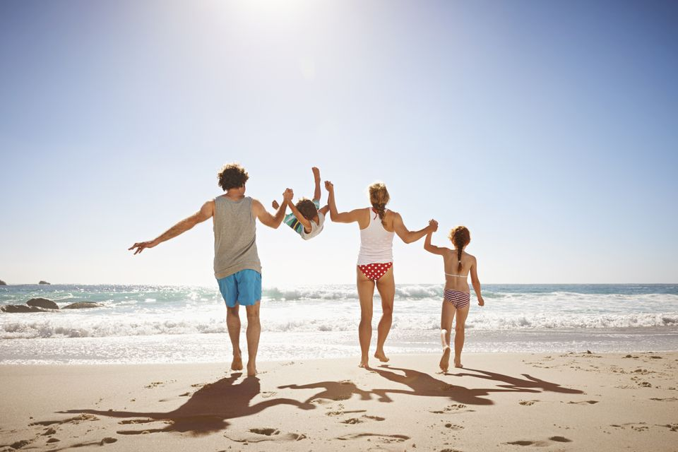Family of four having fun on the beach