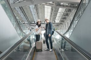 Young Asian couple with luggage down the escalator