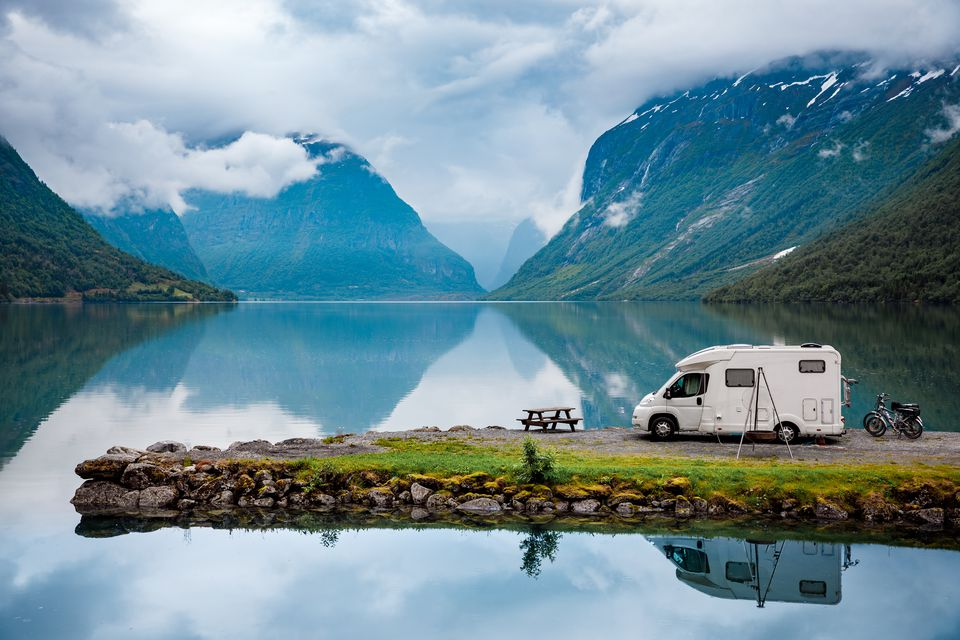 An RV parked lakeside in the Italian Alps