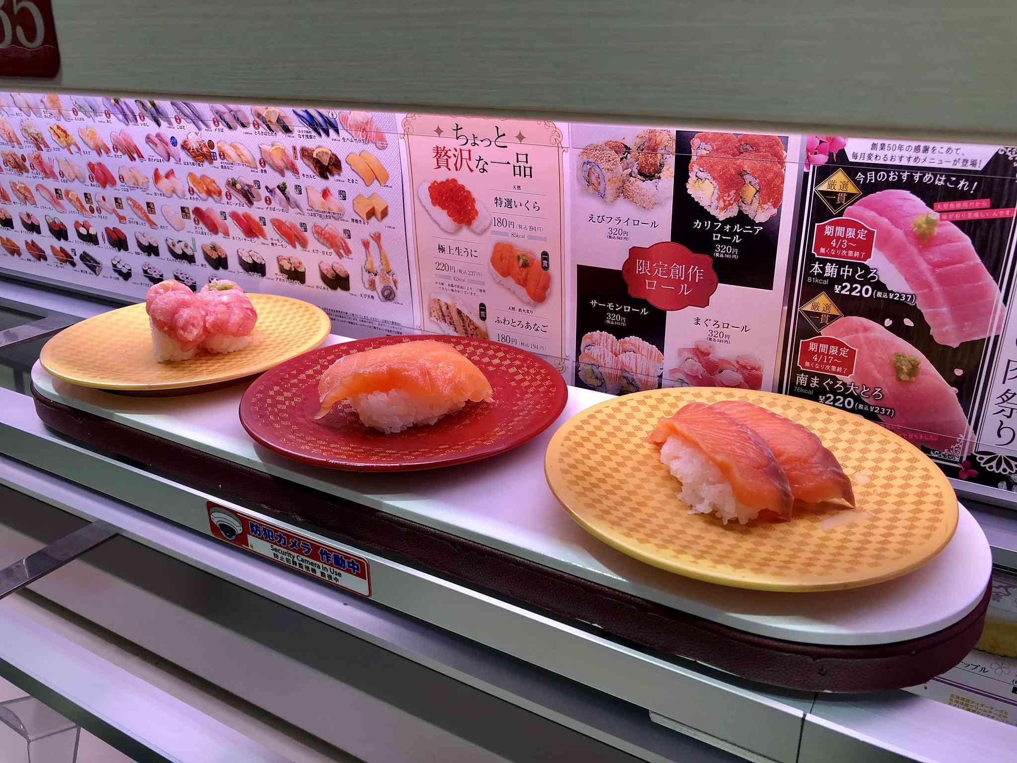 Three pairs of nigiri on three plates on a conveyor belt