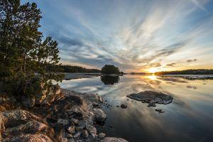 The sun sets over a peaceful lake along a rocky shore