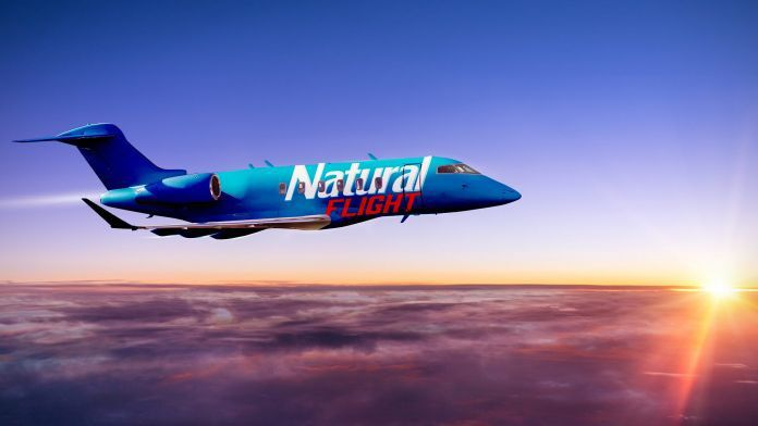 Natural Flight jet flying across sunsetting sky