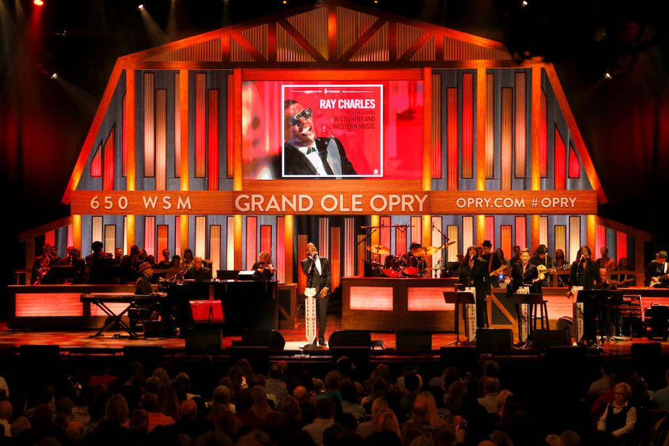 Man singing with a accompanying band and packed audience at The Grand Ole Opry, Nashville