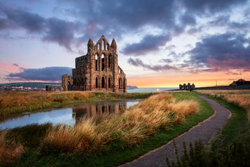 ruins of Whitby abbey at sunset on a cloudy day. The abbey is an field with over grown grasses, a small pond, and a narrow paved footpath