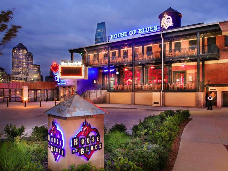 Exterior of the Dallas House of Blues at twilight with signs illuminated