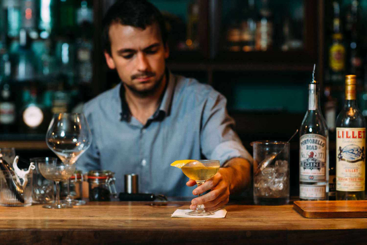 Bartender placing a drink on a napkin at the Ginstitute