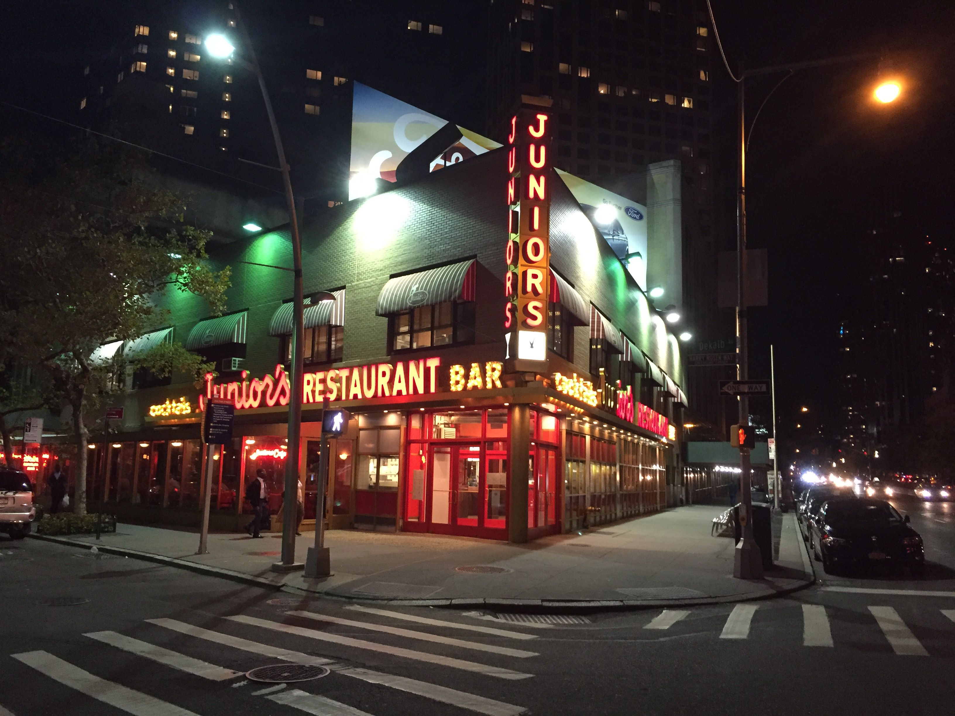 Junior's Restaurant and Bar in Brooklyn lit up at nighttime.