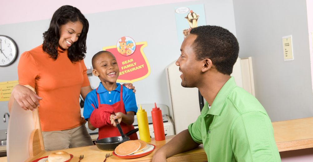 An african american family playing in a pretend kitchen