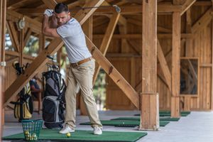 Golf player taking a tee shot at the golf school