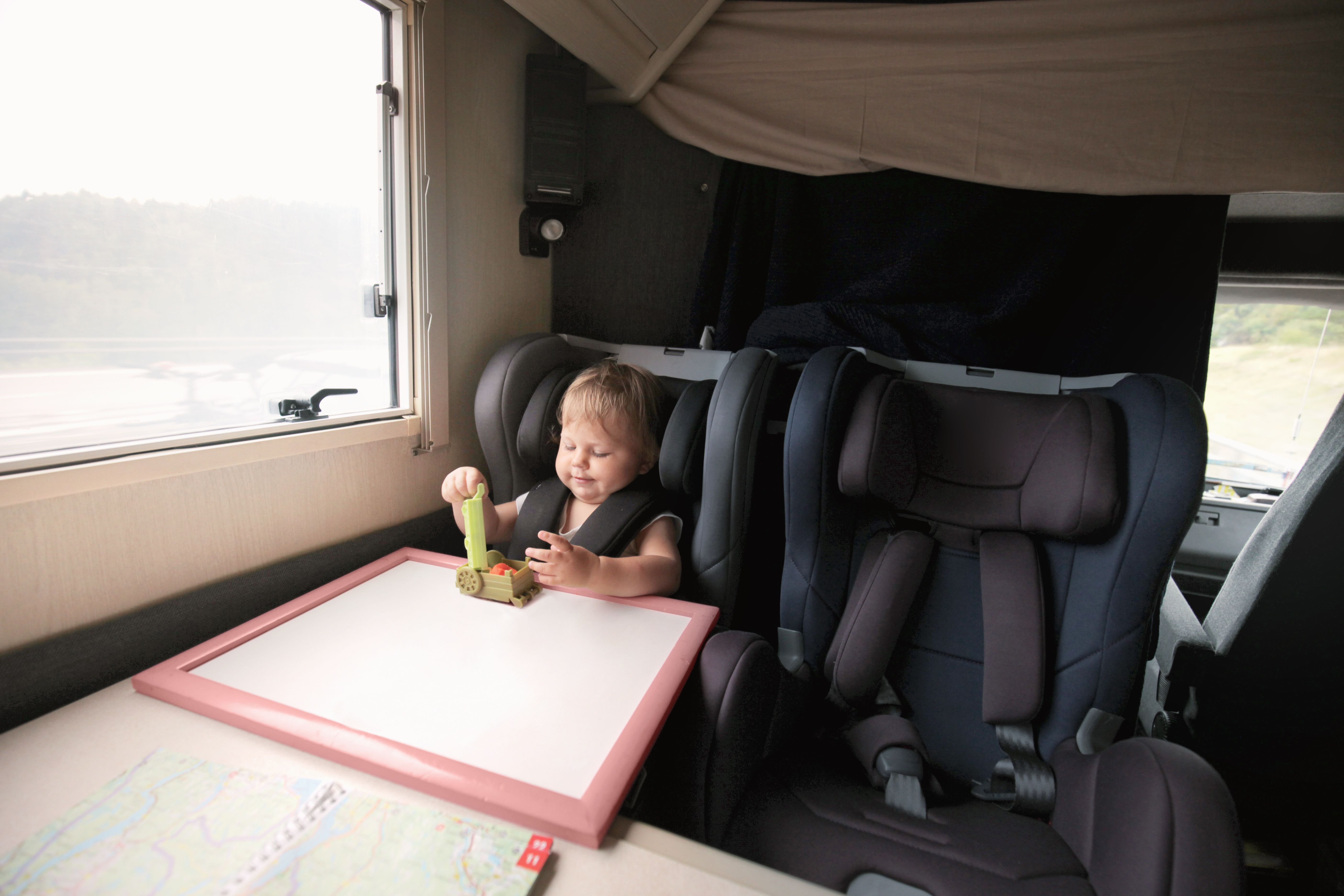Baby in car seat playing during journey in campervan