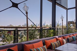 outdoor dining patio with view of the dubai skyline in the far distance. in the foreground is a long gray counch with orange and striped accent pillow. There are lamps and a wire fence behind the couch