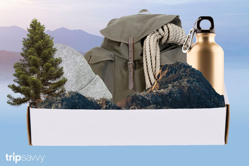 Photo composite of a white cardboard box holding a backpack, beanie and gold water bottle with a carabiner along with a pine tree and some mountains set on a background of a mountain gradient in blue.