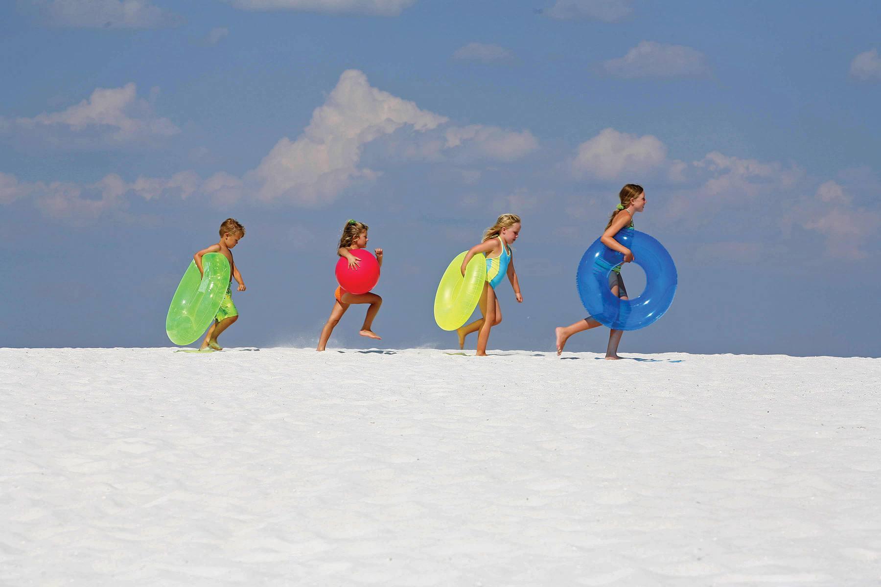 Kinder auf das Wasser am weißen Sandstrand von Panama City Beach marschieren