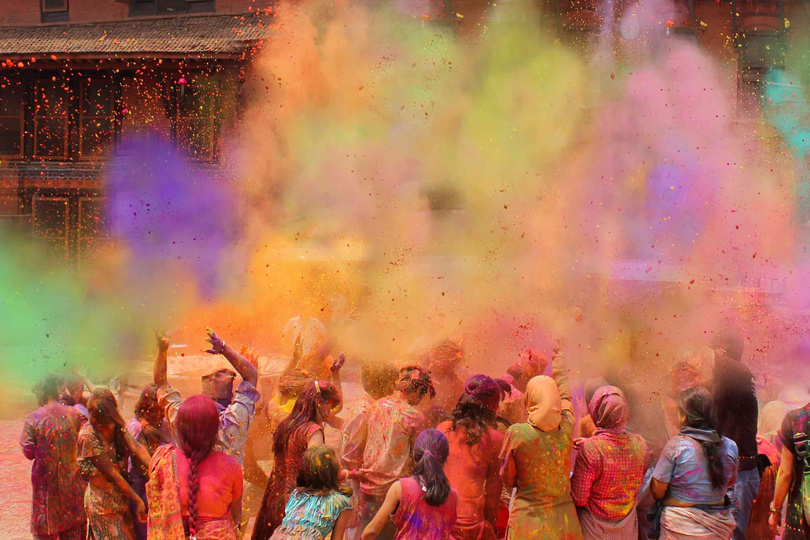 people covered in colored powder throwing colored powder into the air