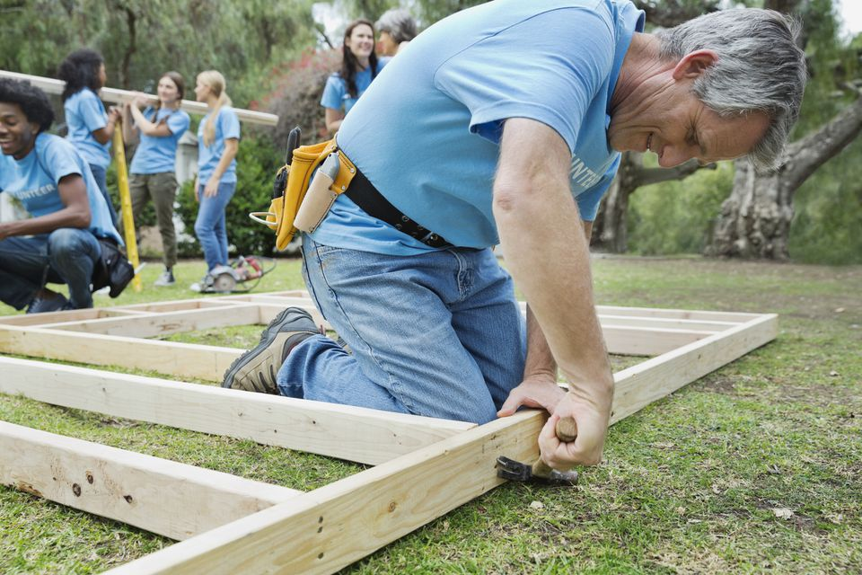 Mature man constructing wooden frame with volunteers in background