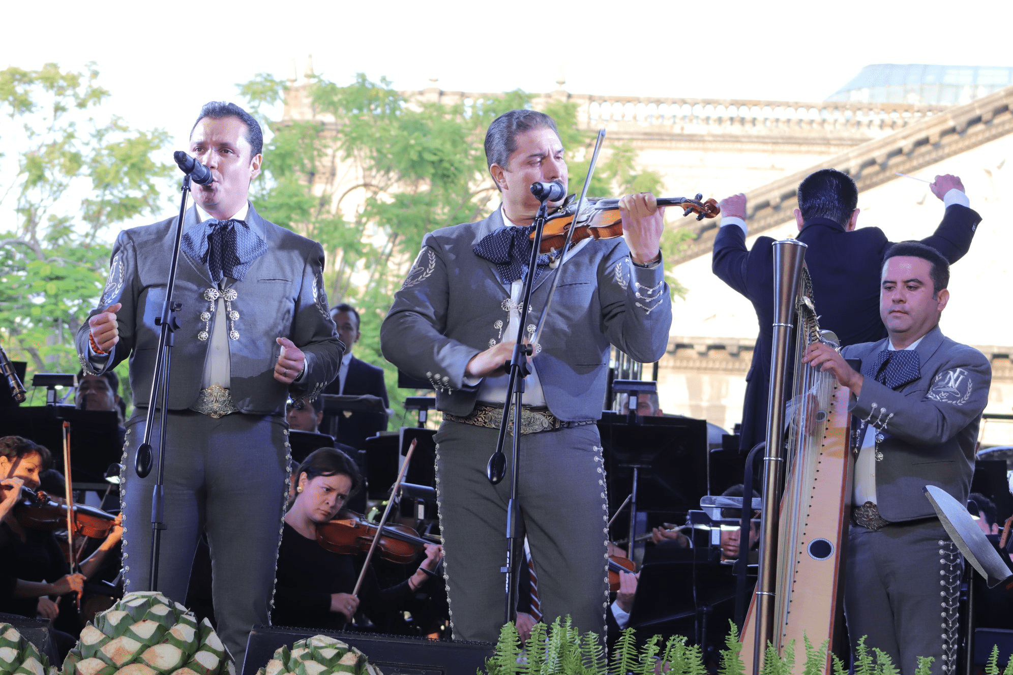 Three-piece mariachi band in grey suits performing on stage with string orchestra