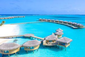 collection of Maldivian overwater bungalows with a light blue ocean beneath them