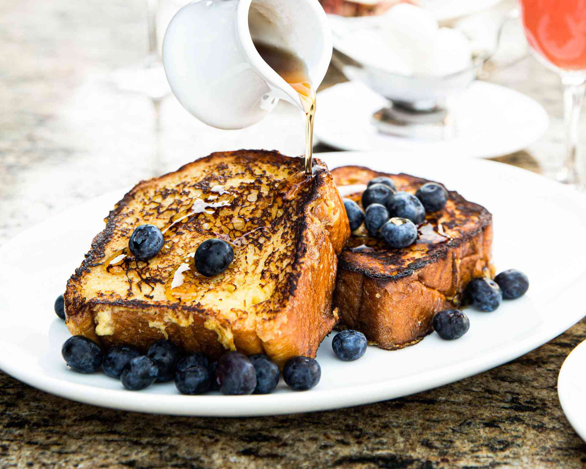 Syrup being poured over two thick pieces of french toast with fresh blueberries