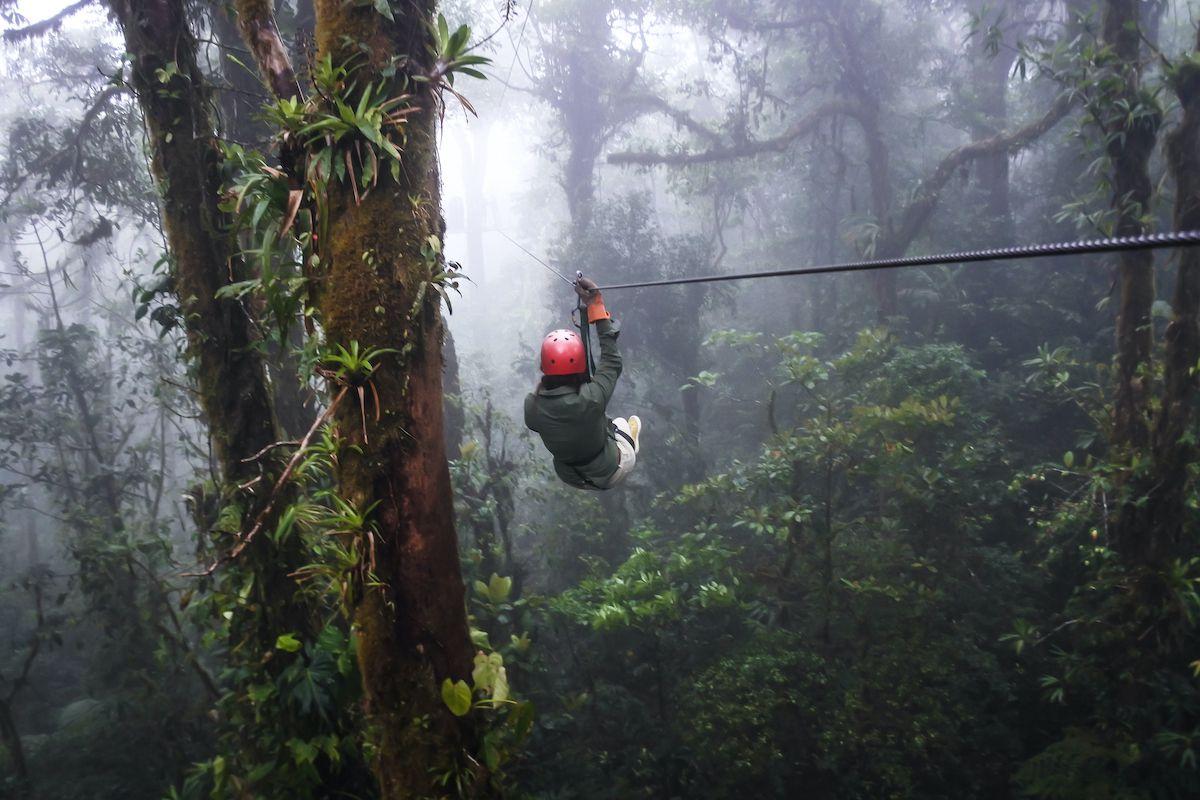 A traveler zip lines through the misty rain forest