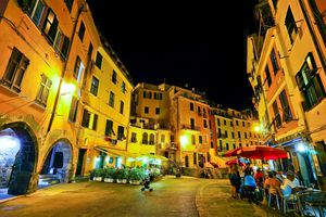 Vernazza's main street at night, with people gathered at a bar