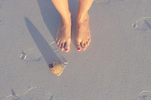 Feet with shell in Florida beach