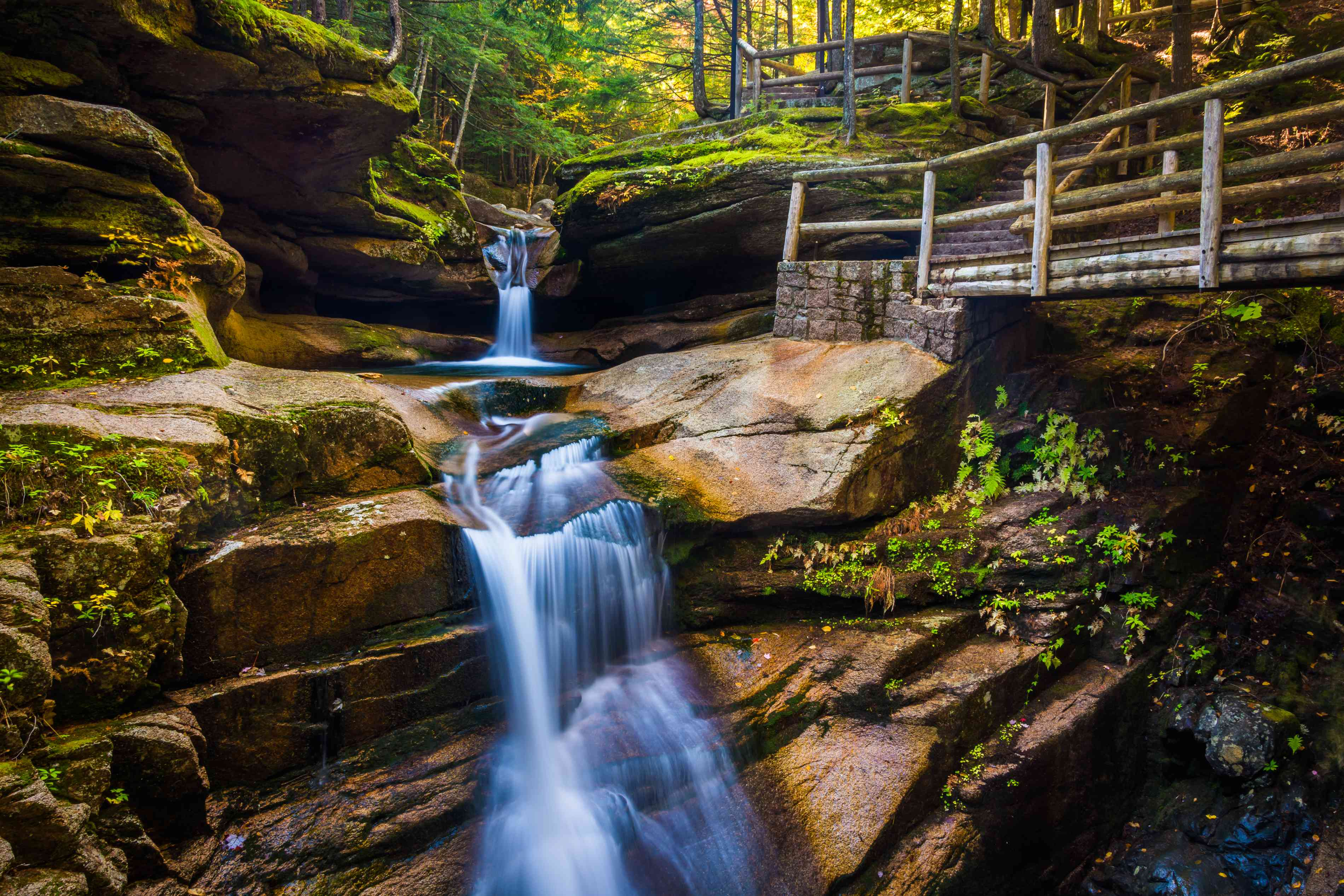 long exposure image of waterfall going down jagged rocks with a wooden trail next to it