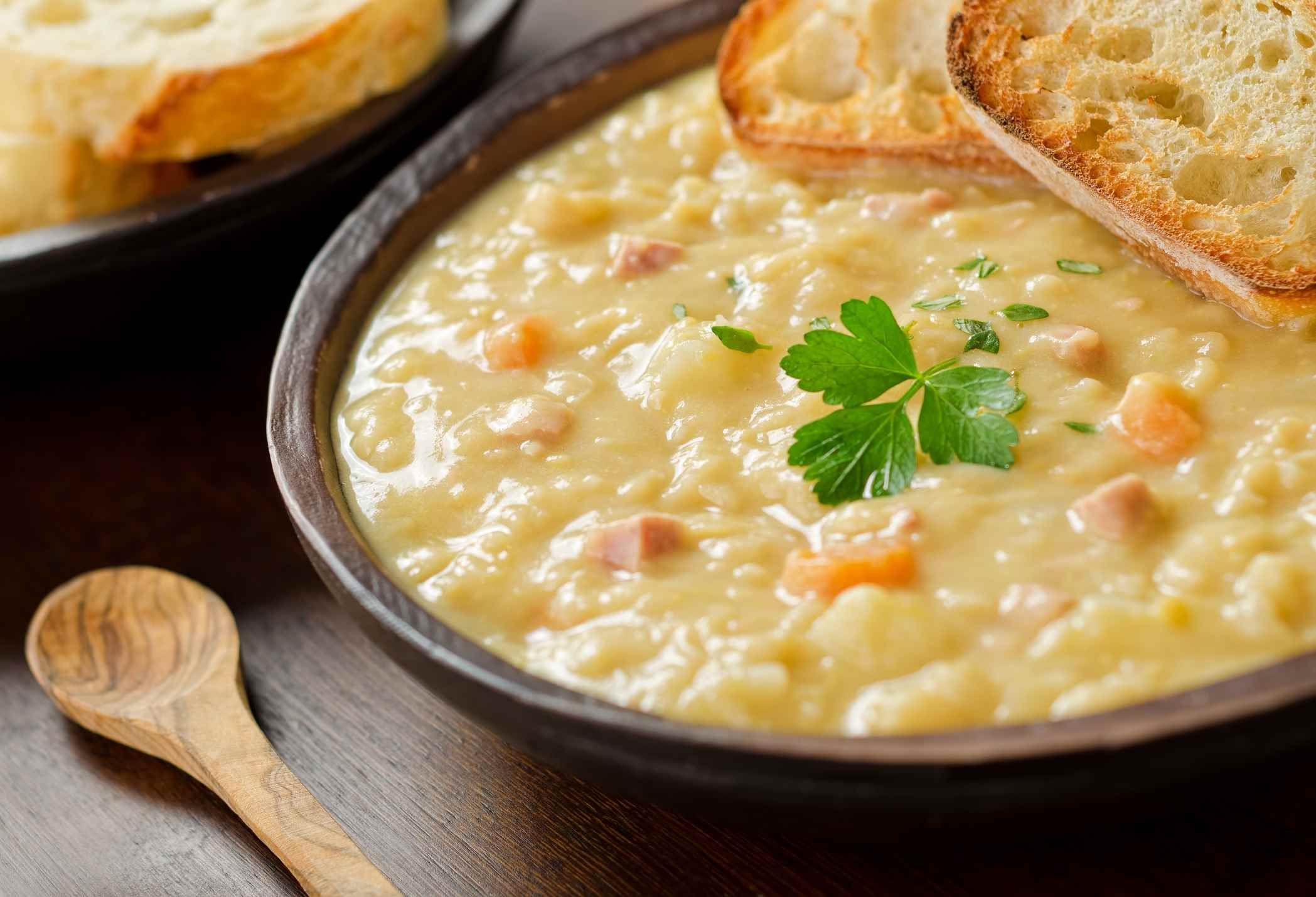 Un plato rústico de sopa de guisantes con jamón ahumado, zanahorias, papa y pan francés