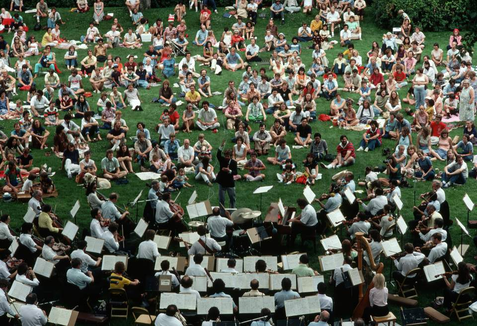 Musicians play an outdoor concert for an audience at the University of Minnesota