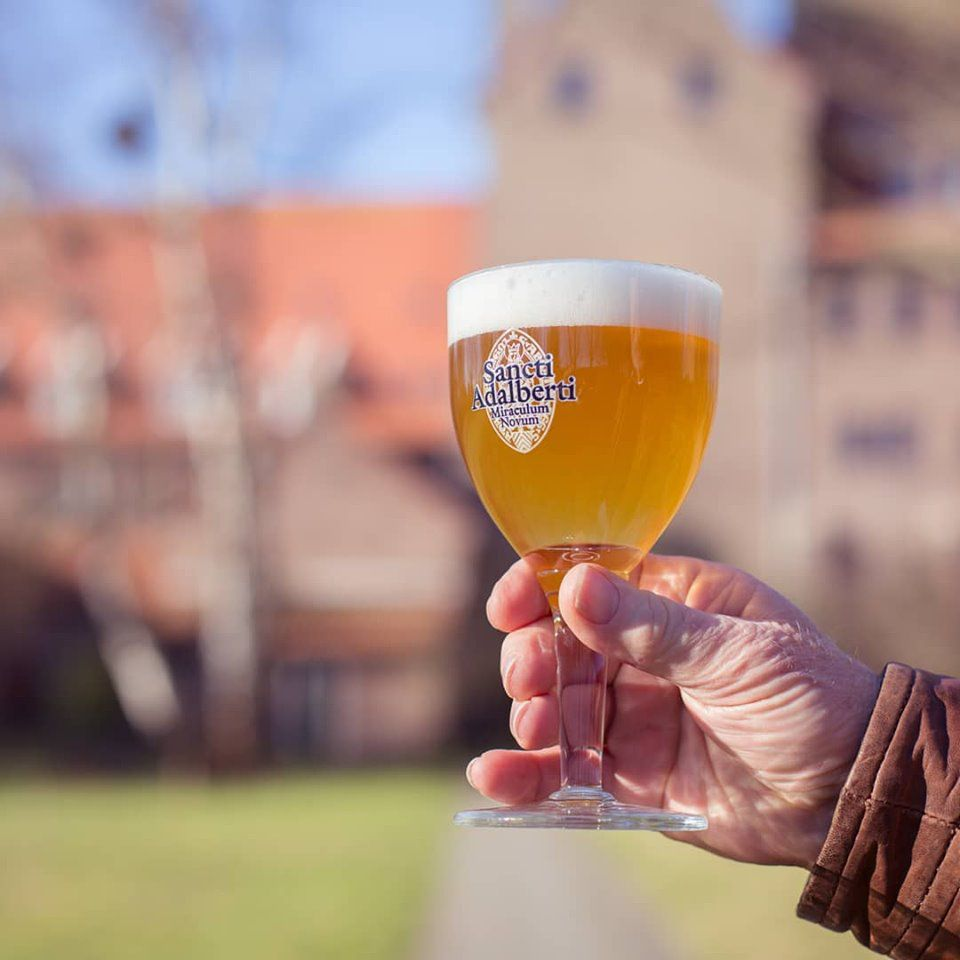 Cropped hand holding a full Sancti Adalberti beer goblet