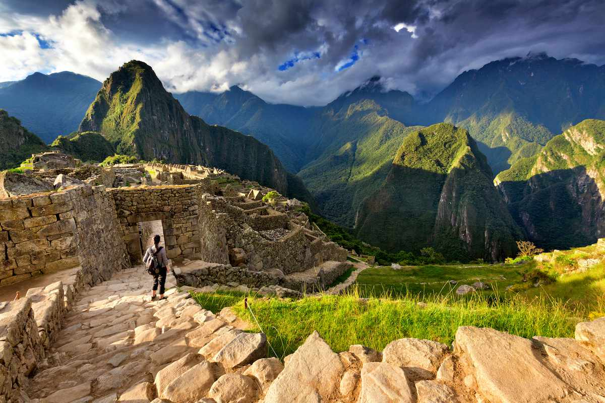 A lone hiker approaches an ancient Incan structure in the mountains