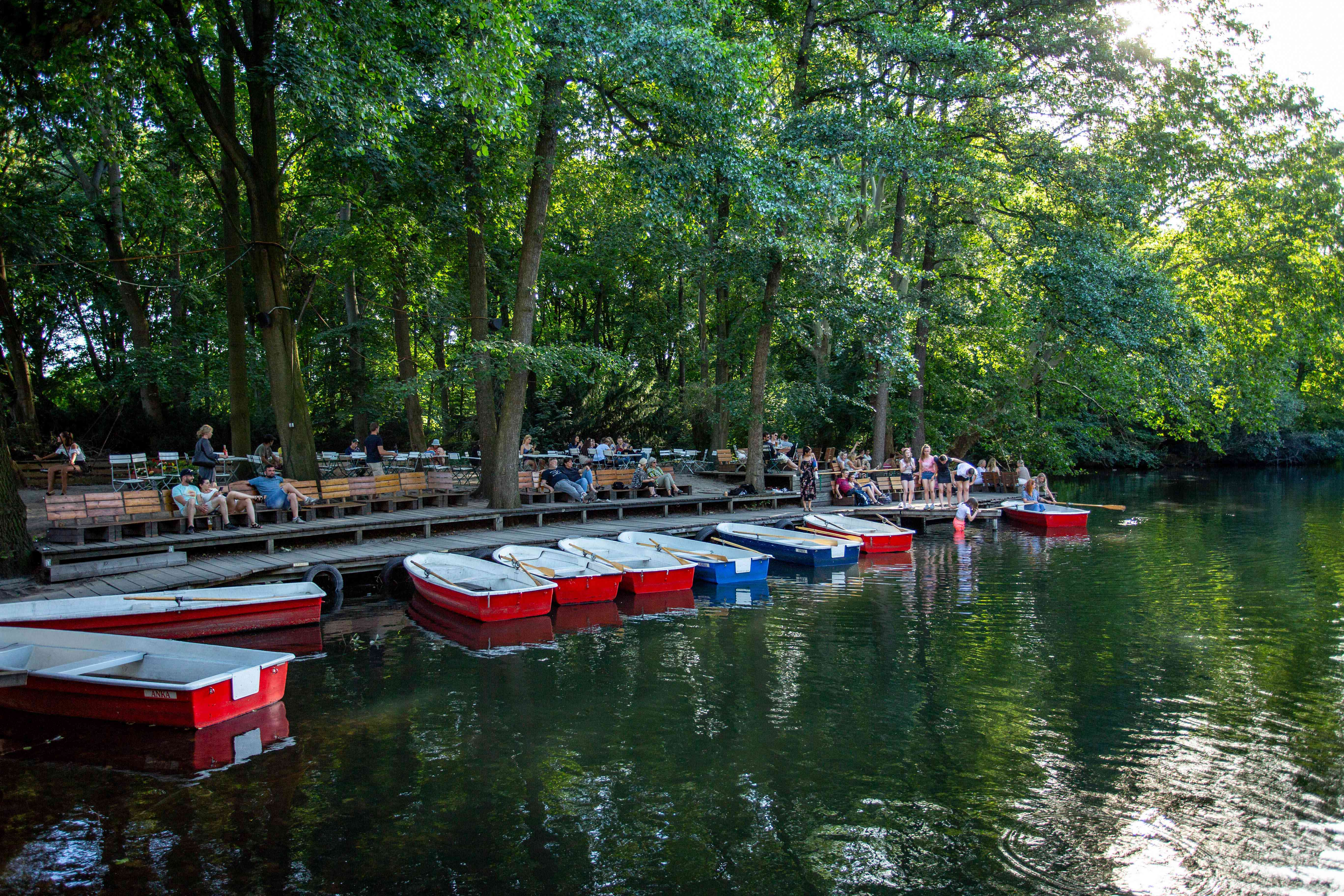 Boats docked by benches at Cafe Am Neuen See