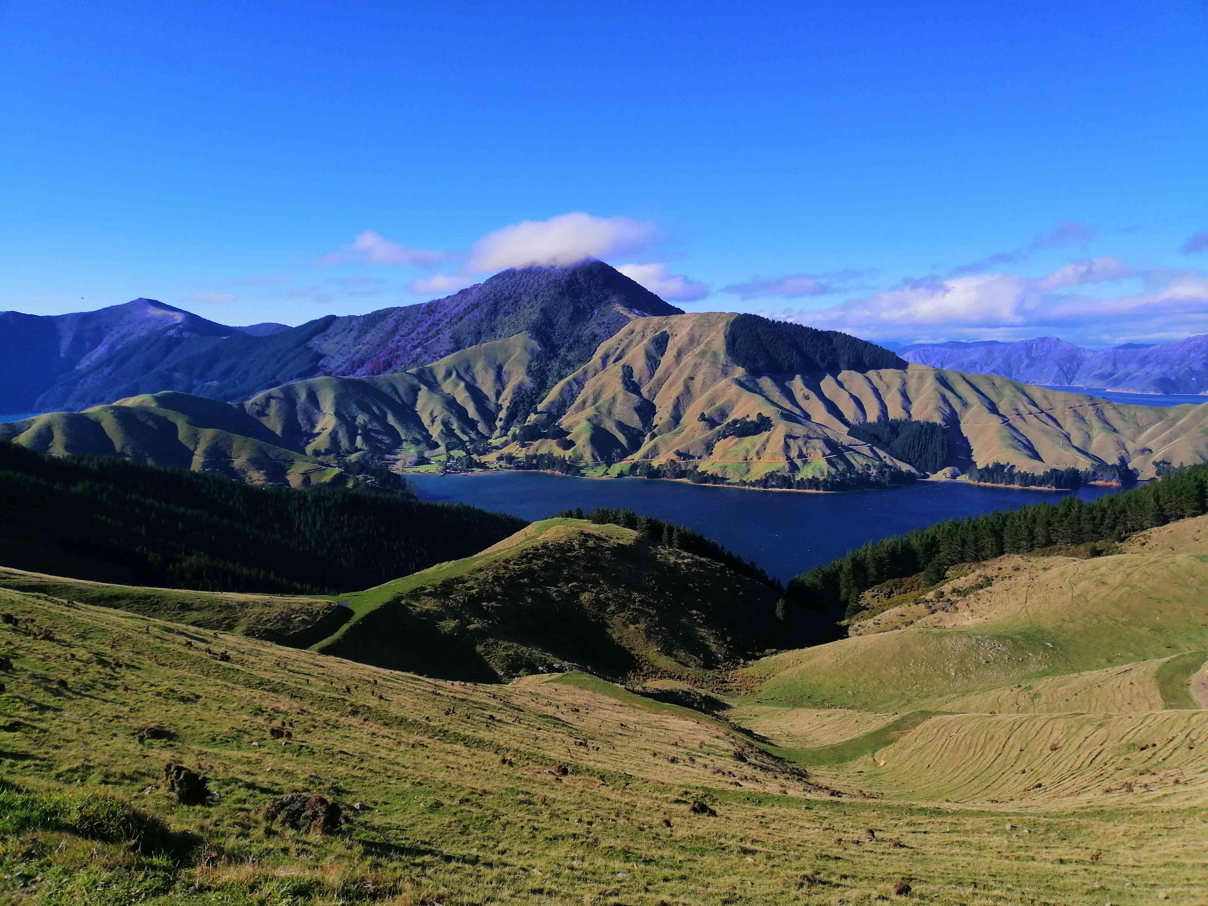 mountains farmland and sea with blue sky