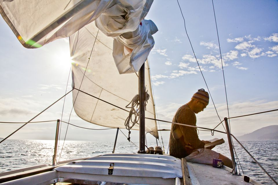 ¿Un joven leyendo en la cubierta de un velero