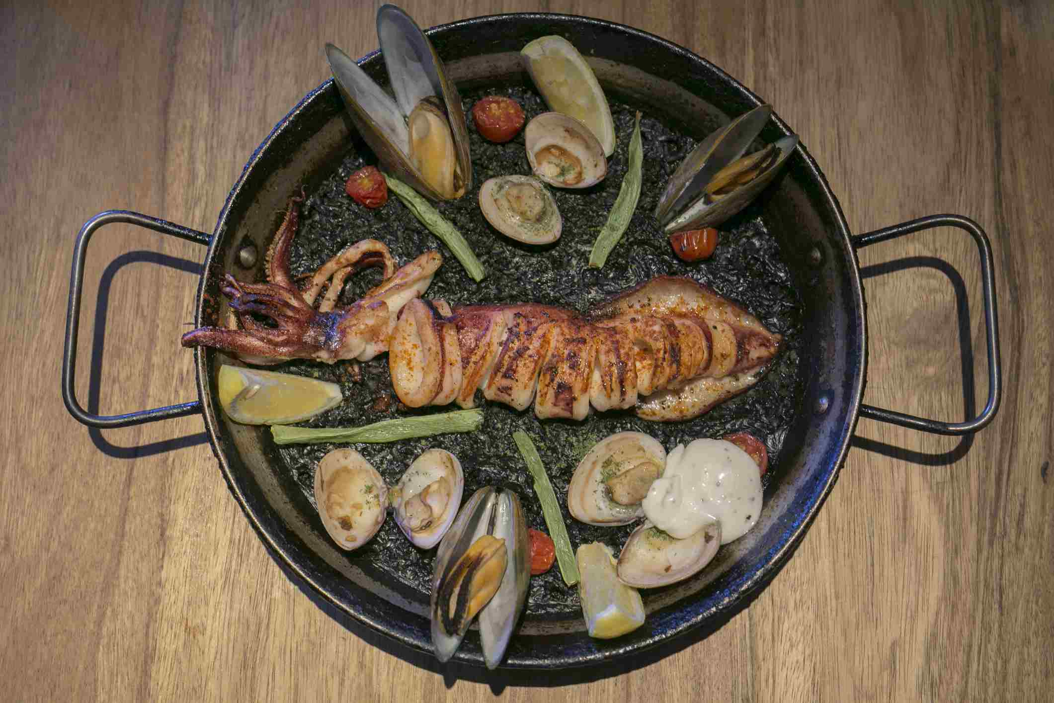 Aerial View of Spainish Seafood Paella, Black risotto with Roast Seafood and Dark Cuttlefish Sauce