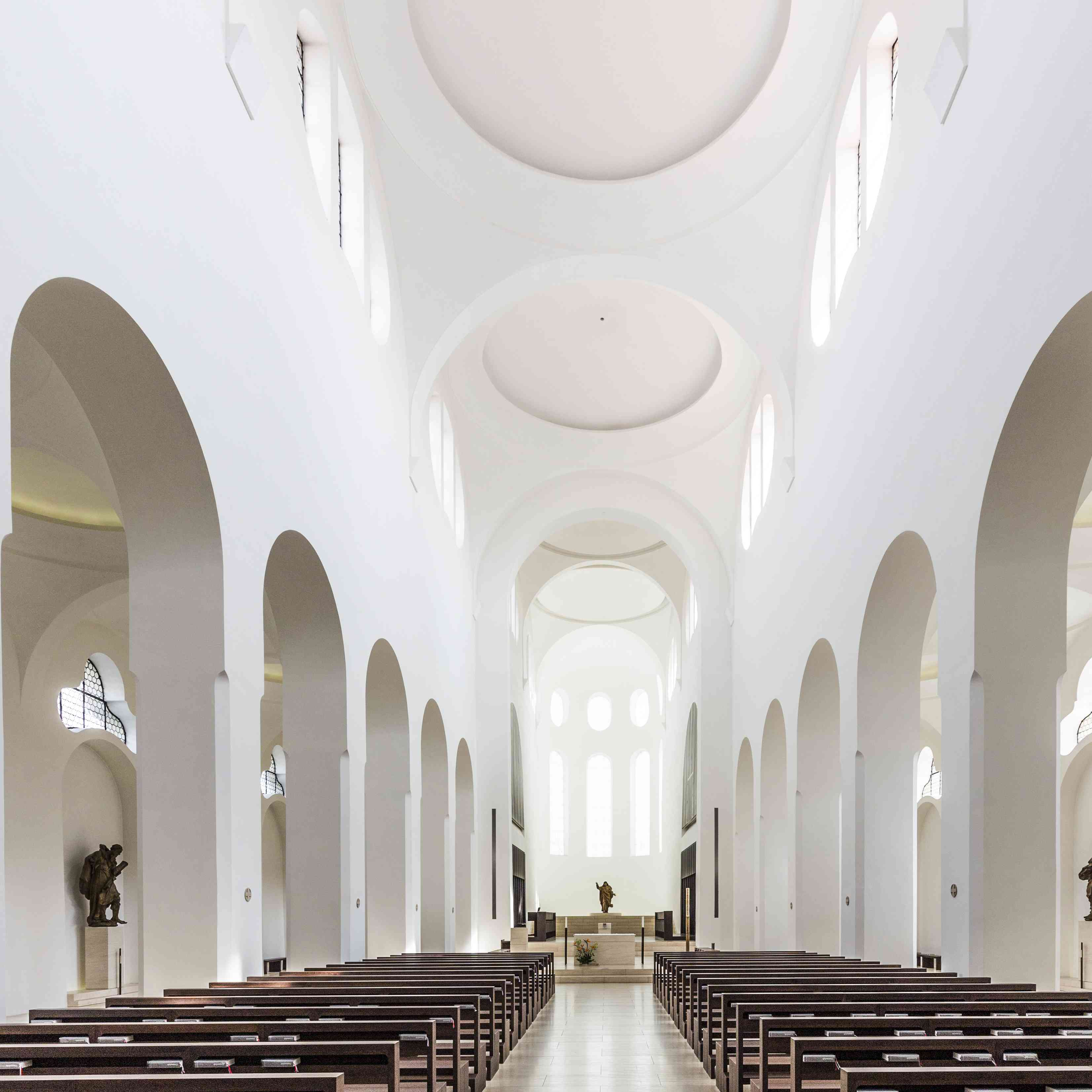 church with white minimalist design and simple, dark wooden benches